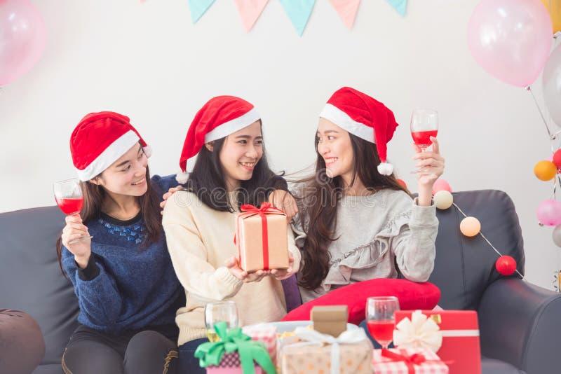 Trois belles filles asiatiques célébrant Noël avec du vin image libre de droits