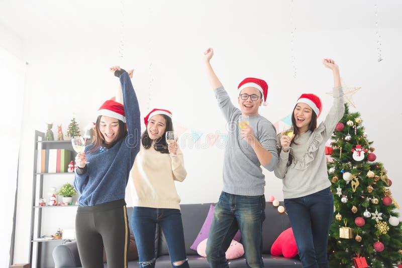 Trois belles filles asiatiques et un homme célébrant Noël avec du vin image libre de droits