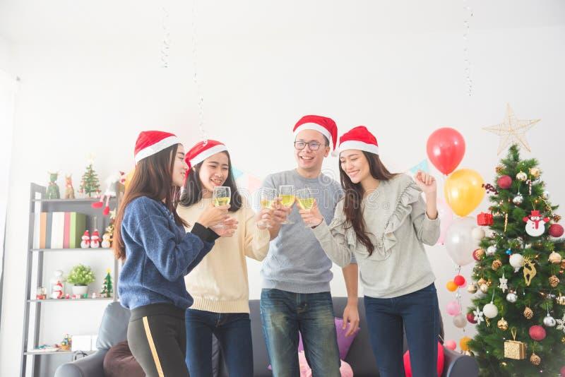 Trois belles filles asiatiques et un homme célébrant Noël avec du vin photographie stock libre de droits