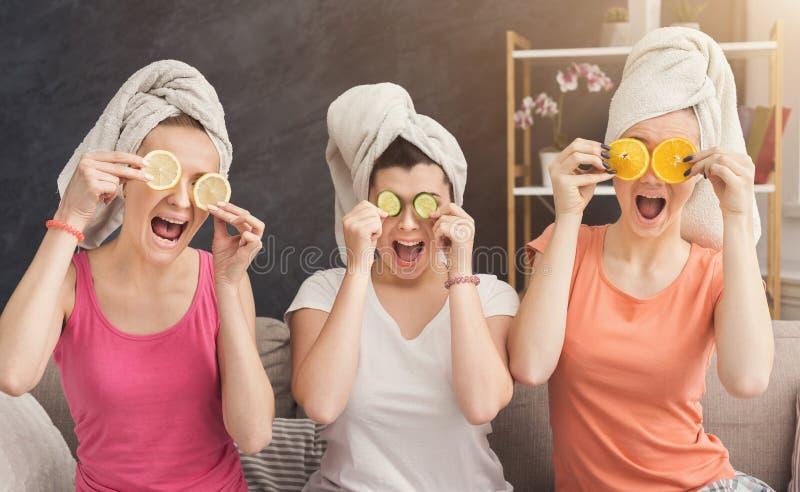 Trois belles filles couvrant des yeux de morceaux de fruit image libre de droits