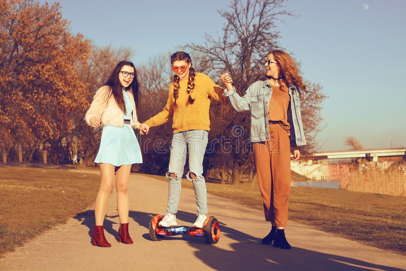 Trois belles filles dans le hoverboard Relations d'amies, promenade, technologies modernes actives et nouvelles Les filles enseig photographie stock