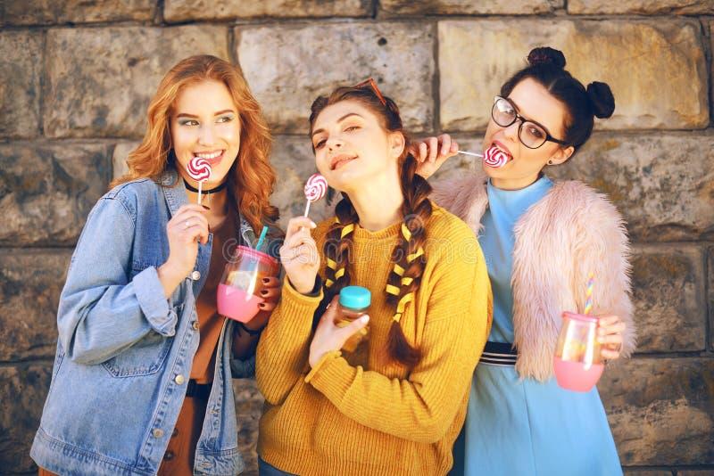 Trois belles filles manger des lucettes et boire le lemonad dans la bouteille rose Amies avec différentes coiffures Amis, femme photo stock