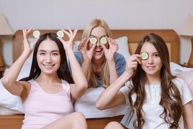 trois belles filles multi-ethniques couvrant des yeux de concombre photos stock