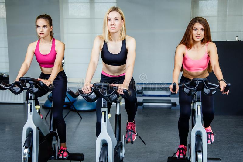 Trois belles jeunes femmes établissant sur des vélos au gymnase photos stock