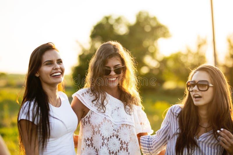 Trois belles jeunes femmes aux cheveux foncés dans des lunettes de soleil habillées dans les beaux vêtements sourient et marchent image libre de droits