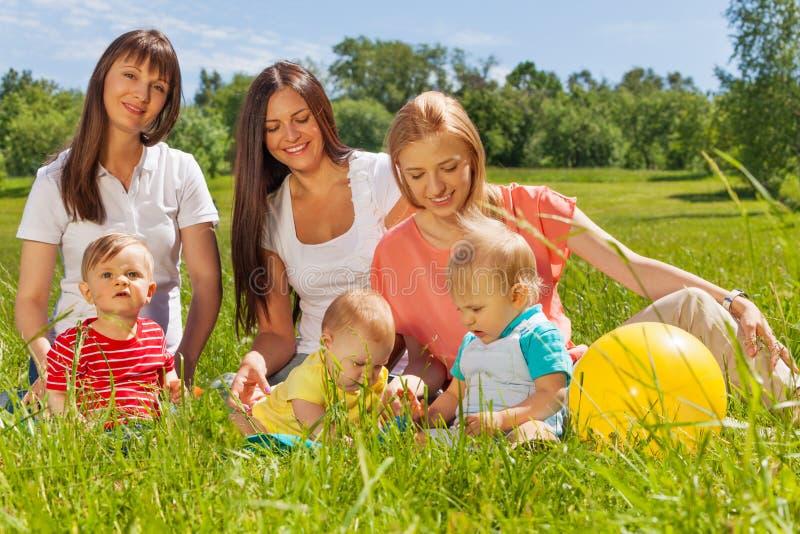 Trois belles mères heureuses avec se reposer de bébés photographie stock libre de droits