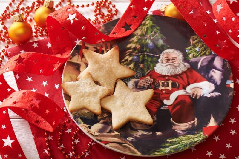 Trois biscuits sous forme d'étoile du plat décoratif entouré par des décorations de Noël image libre de droits