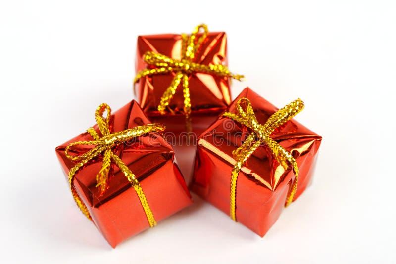 Trois boîte-cadeau brillants rouges avec de l'or cintrent sur le fond blanc image libre de droits