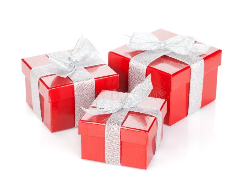 Trois boîte-cadeau rouges avec le ruban et l'arc argentés photographie stock