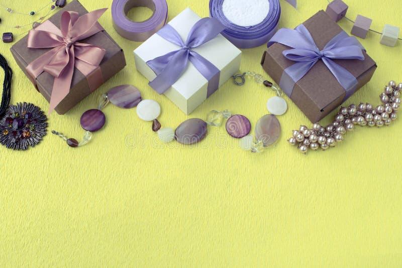 Trois boîtes décoratives avec des cadeaux sur le ruban jaune de satin cintrent le fond Accessoires de mode de bijoux du ` s de fe photo libre de droits