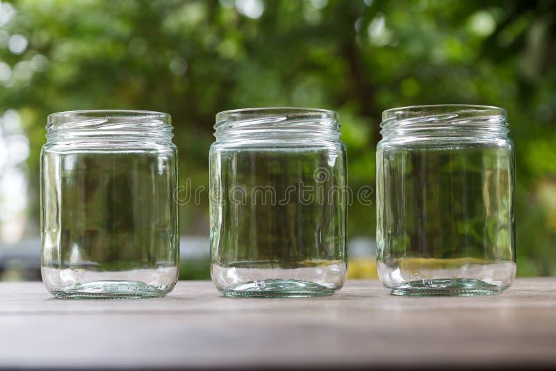Trois boîtes métalliques en verre vides de forme ronde sur le bureau en bois avec le fond de nature photos stock