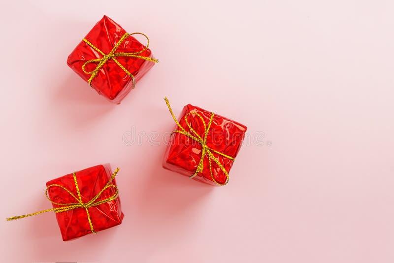 Trois boîtes rouges avec des cadeaux sur un fond en pastel rose, configuration plate de fête, vue supérieure, l'espace de copie images libres de droits