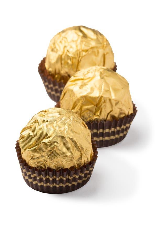 Trois bonbons au chocolat d'isolement dans l'aluminium d'or image stock