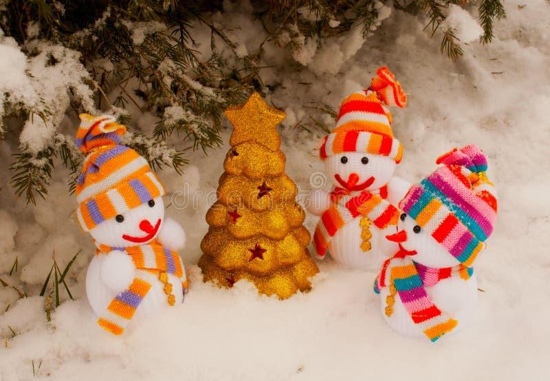 Trois bonhommes de neige avec l'arbre toujours d'actualité d'or images libres de droits
