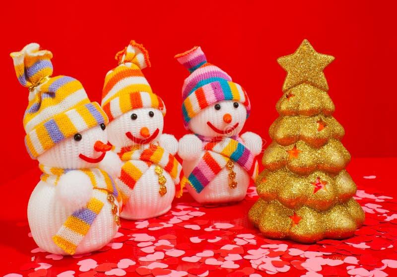 Trois bonhommes de neige avec l'arbre toujours d'actualité d'or image stock