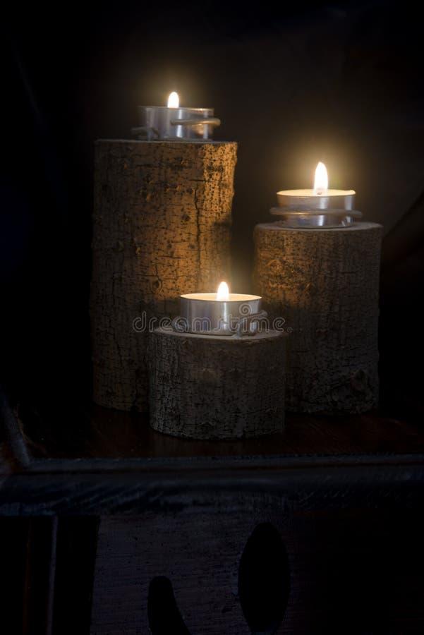 Trois bougies allumées dans des chandeliers en bois images libres de droits