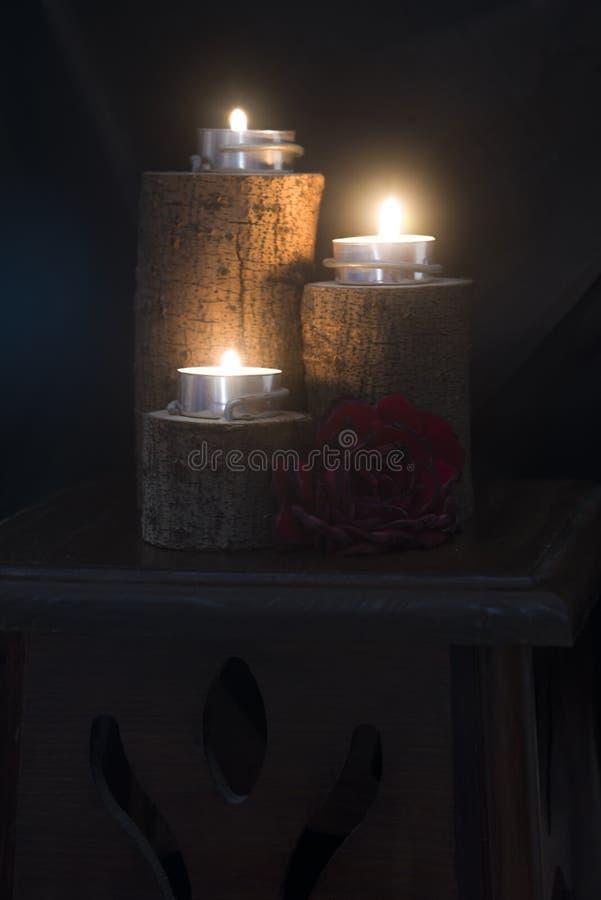 Trois bougies allumées dans des chandeliers en bois photos stock