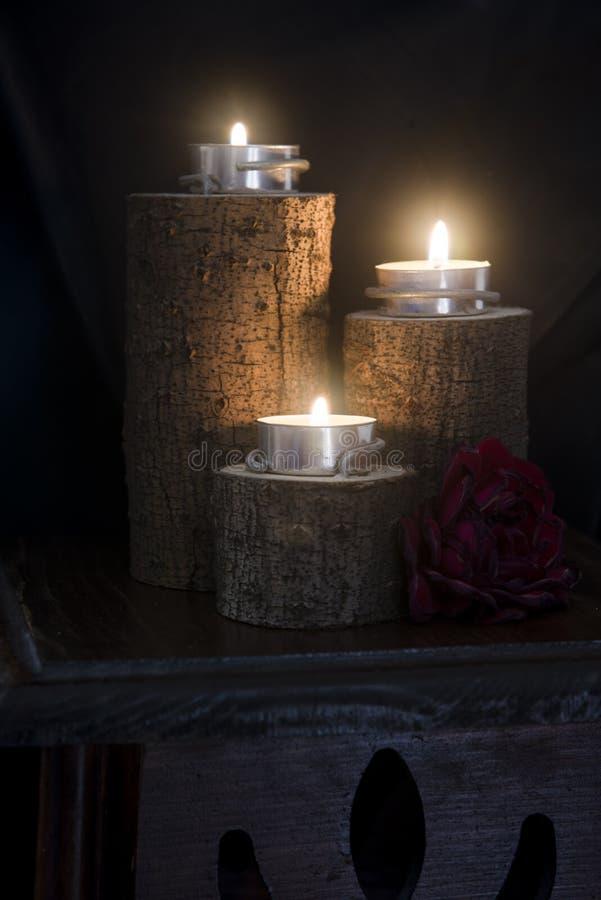 Trois bougies allumées dans des chandeliers en bois image libre de droits