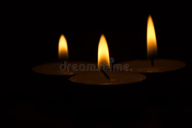 Trois bougies allumées sur un fond noir image libre de droits