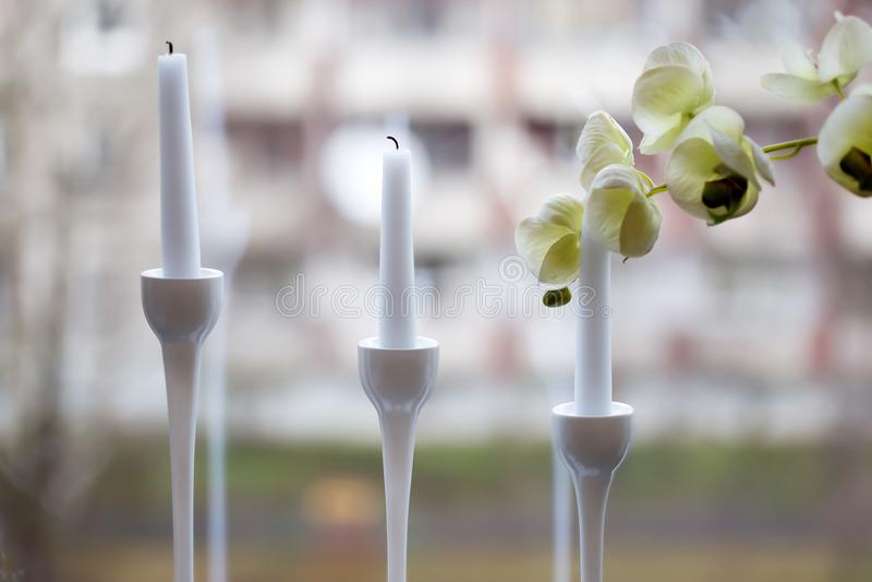 Trois bougies blanches dans le bougeoir élégant avec une orchidée se développent photographie stock libre de droits