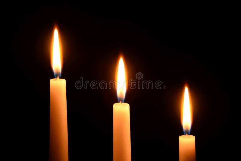 Trois bougies blanches sur un fond noir image libre de droits