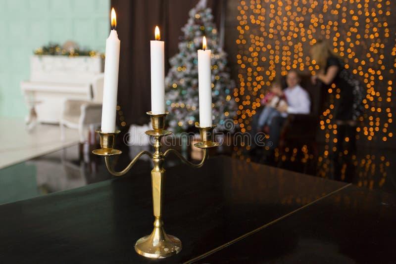 Trois bougies brûlantes dans le bougeoir d'or sur la table noire à l'arrière-plan des silhouettes de la famille - parents et enfa photographie stock libre de droits