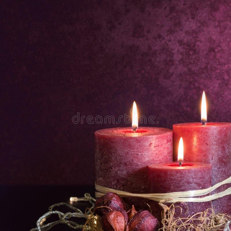 Trois bougies dans le pourpre photographie stock