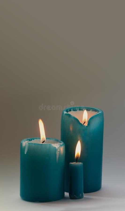 Trois bougies de turquoise sur le fond gris Foyer mou, l'espace de copie, photo verticale photo stock