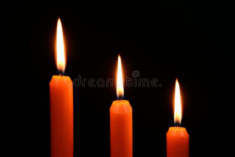 Trois bougies oranges sur un fond noir photos stock