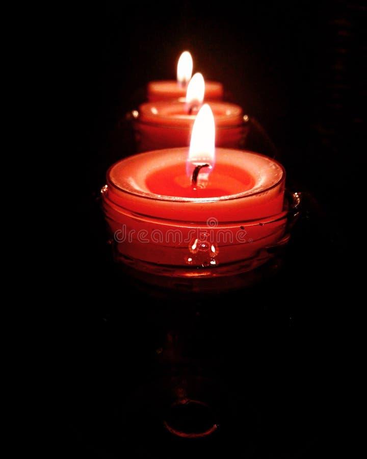 Trois bougies roses brûlant brillamment sur le fond noir photographie stock libre de droits