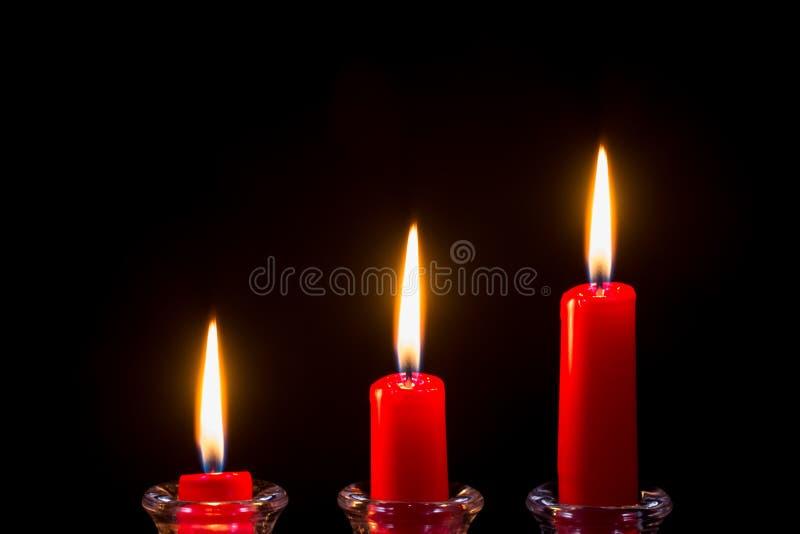 Trois bougies rouges sur un fond noir image stock