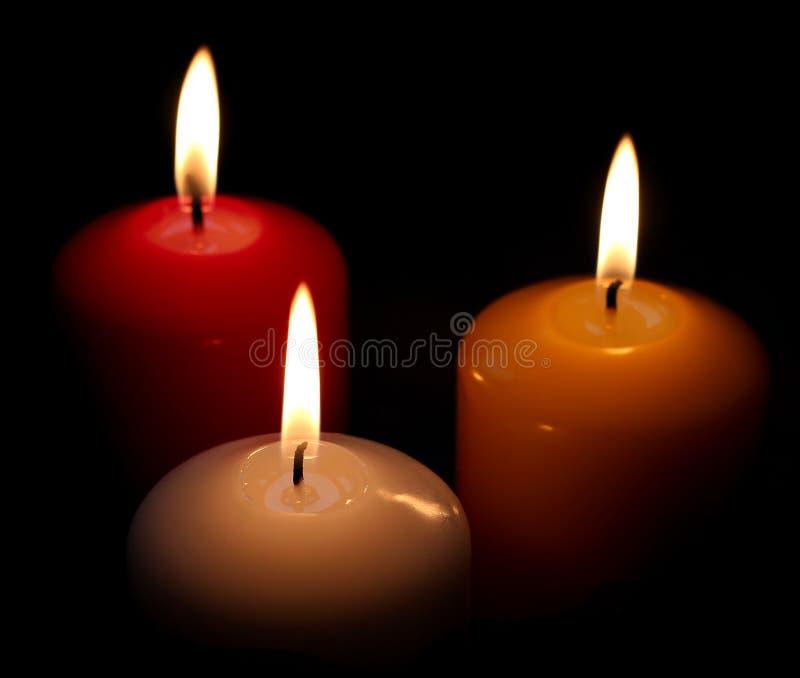 Trois bougies sur le fond noir images stock