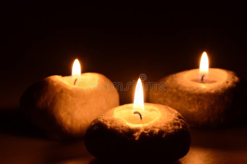 Trois bougies sur un fond noir photo stock