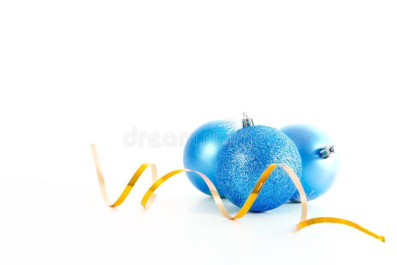 Trois boules bleues de Noël avec le ruban d'or d'isolement sur un fond blanc photos stock