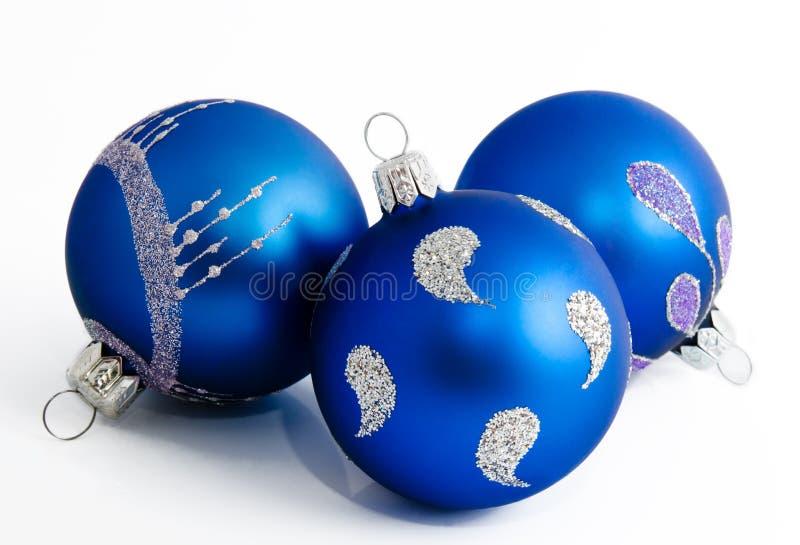 Trois boules bleues de Noël d'isolement sur un blanc image libre de droits