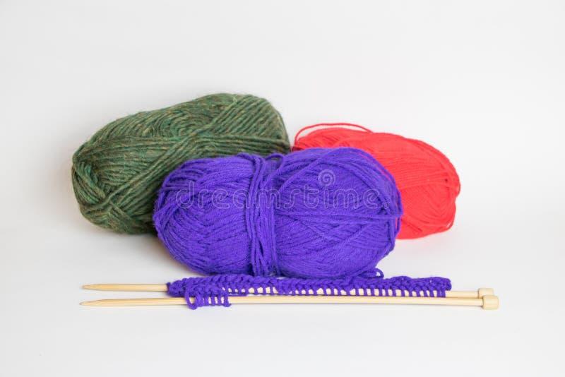 Trois boules colorées de fil avec deux aiguilles de tricotage photos libres de droits