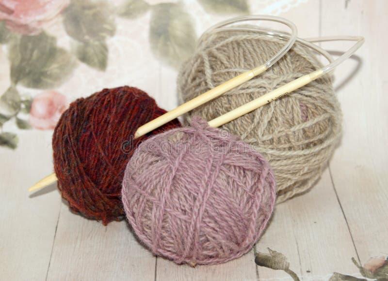 Trois boules colorées de fil de laine avec les aiguilles en bois photographie stock libre de droits