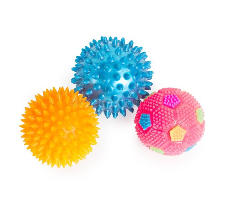 Trois boules en caoutchouc de massage avec des épines rose, bleu, isolant jaune images libres de droits