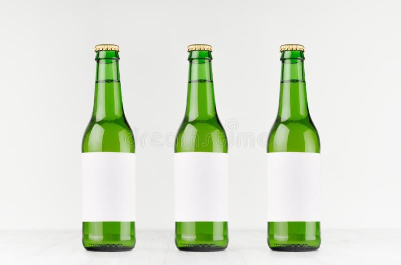 Trois bouteilles à bière vertes de longneck 330ml avec le label blanc vide sur le conseil en bois blanc, raillent  photo stock