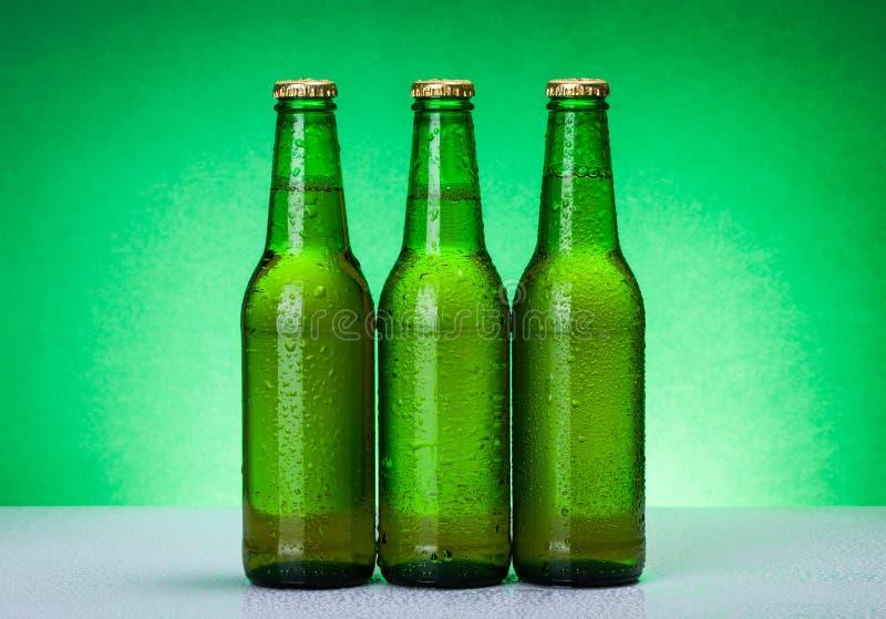 Trois bouteilles à bière vides humides images stock