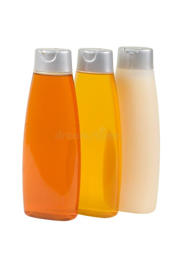 Trois bouteilles avec le nettoyeur et le shampooing photos libres de droits