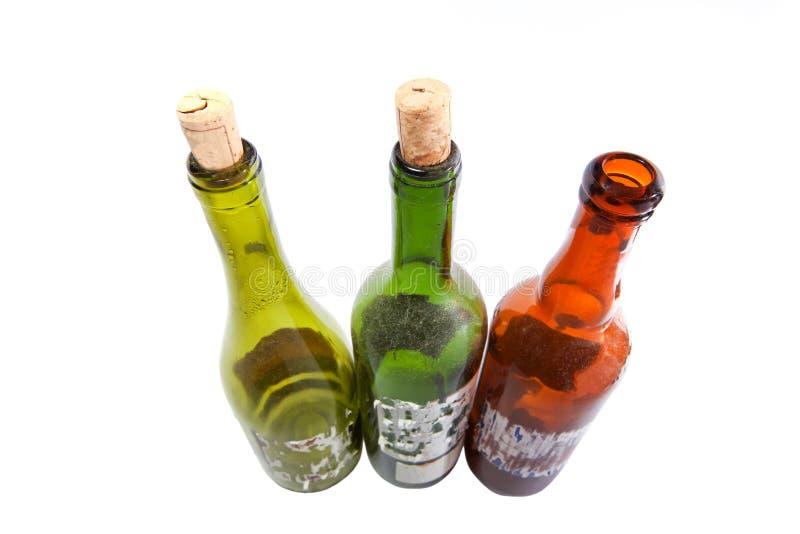 Trois bouteilles de vin poussiéreuses d'isolement sur le blanc image stock