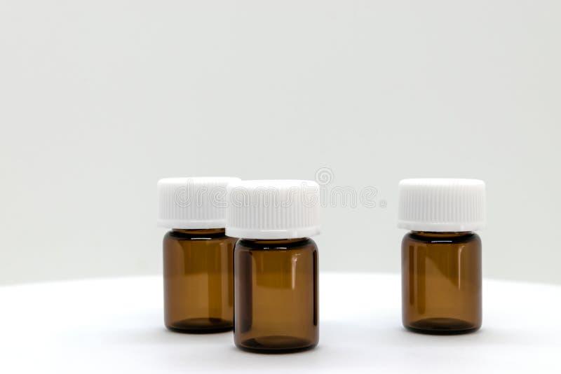 Trois bouteilles témoin de Brown avec les chapeaux blancs sur le fond blanc avec l'espace libre photographie stock