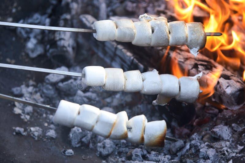 Trois brochettes des guimauves grillant sur un feu photographie stock