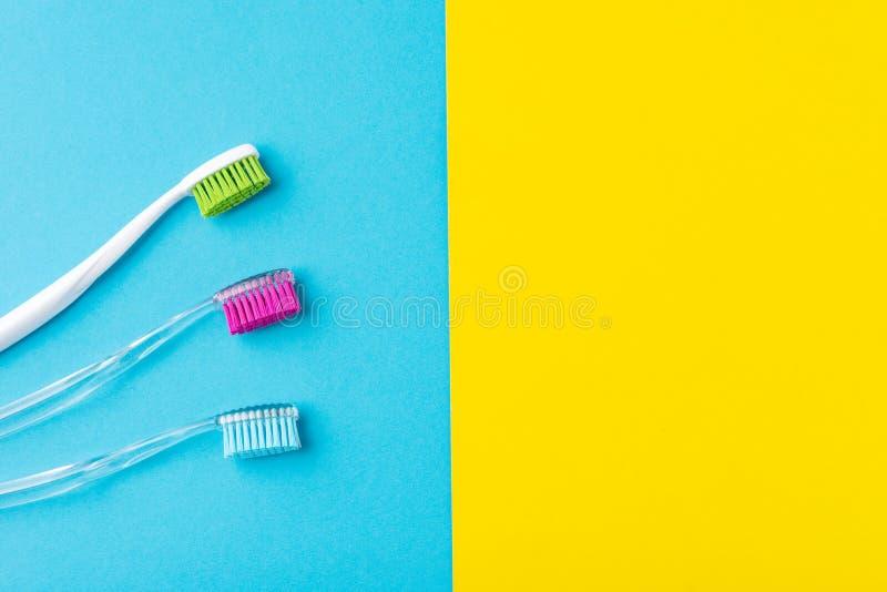 Trois brosses à dents en plastique sur un bleu coloré et un fond jaune, fin  photo stock
