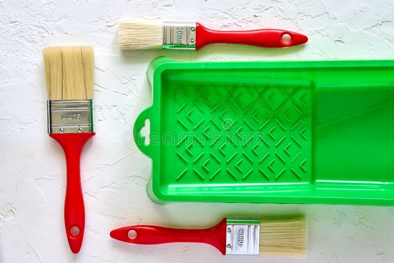 Trois brosses avec les poignées rouges et le plateau vert de peinture sur le fond concret blanc Outils et accessoires pour la r?n photographie stock libre de droits