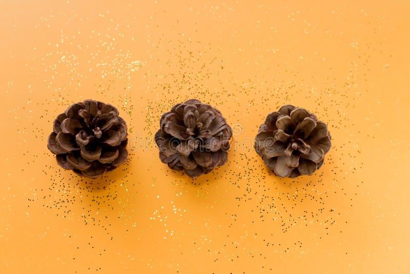 Trois cônes de pin sur un fond orange de scintillement Configuration plate image stock