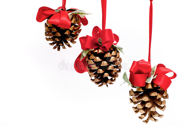 Trois cônes de pin pendant des rubans rouges photographie stock