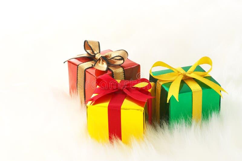 Trois cadeaux sur la fourrure fausse blanche. (horizontal) photo stock