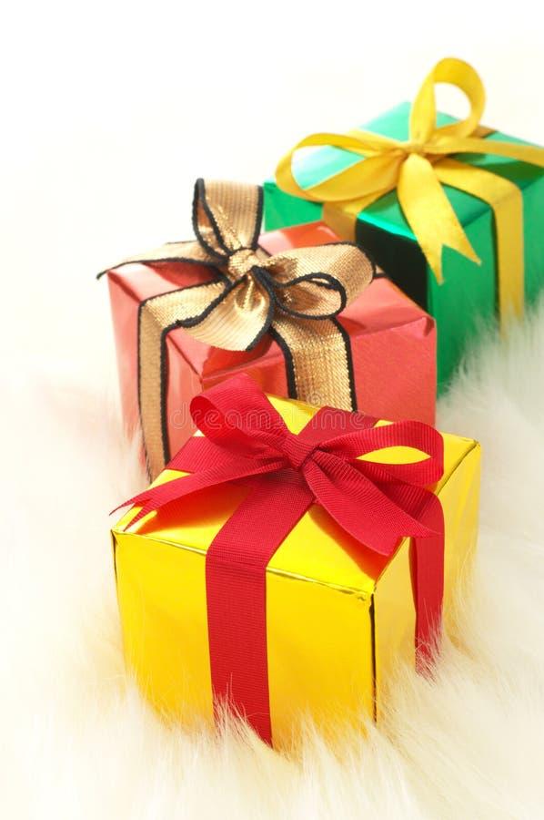 Trois cadeaux sur la fourrure fausse blanche. (verticale) images stock